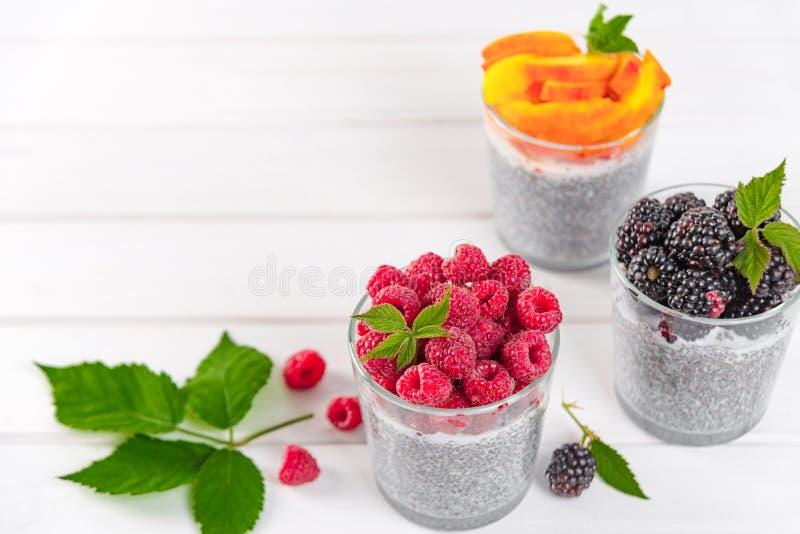 Voedsel en drank, het gezond eten en het op dieet zijn concept Eigengemaakte witte chiapudding met verse bessen en groene bladere royalty-vrije stock fotografie