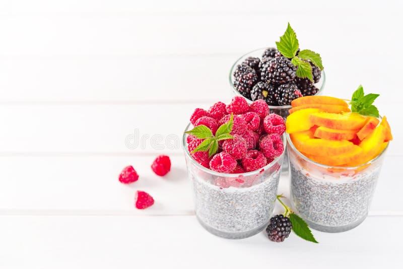 Voedsel en drank, het gezond eten en het op dieet zijn concept Eigengemaakte witte chiapudding met verse bessen en groene bladere stock foto