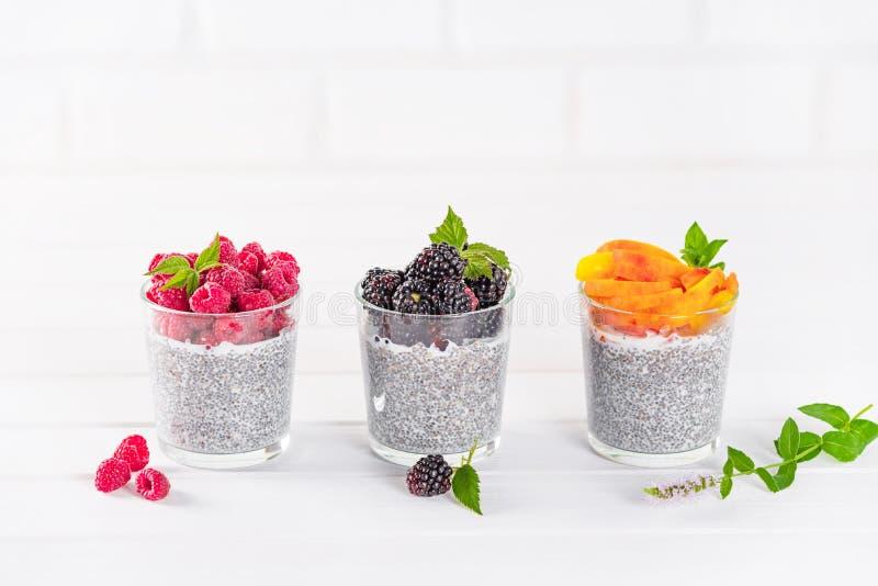 Voedsel en drank, het gezond eten en het op dieet zijn concept Eigengemaakte witte chiapudding met verse bessen en groene bladere stock foto's