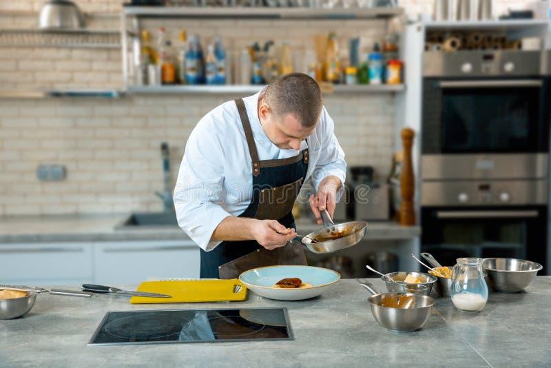 Voedsel het koken, beroep en mensenconcept - de mannelijke dienende plaat van de chef-kokkok van polenta en kalfsvleestongen met  stock foto