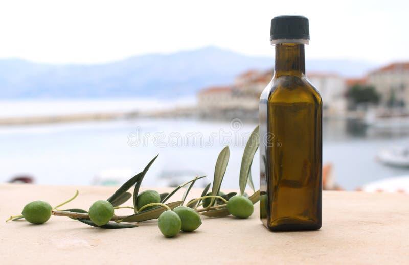 Voedsel het stileren van olijfoliefles en olijven op marmeren lijst Vage achtergrond stock fotografie