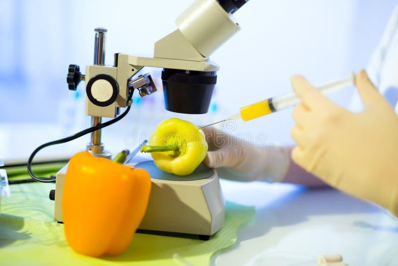 Voedsel het testen in het laboratorium Injectie in banaan die op witte achtergrond wordt geïsoleerd stock foto