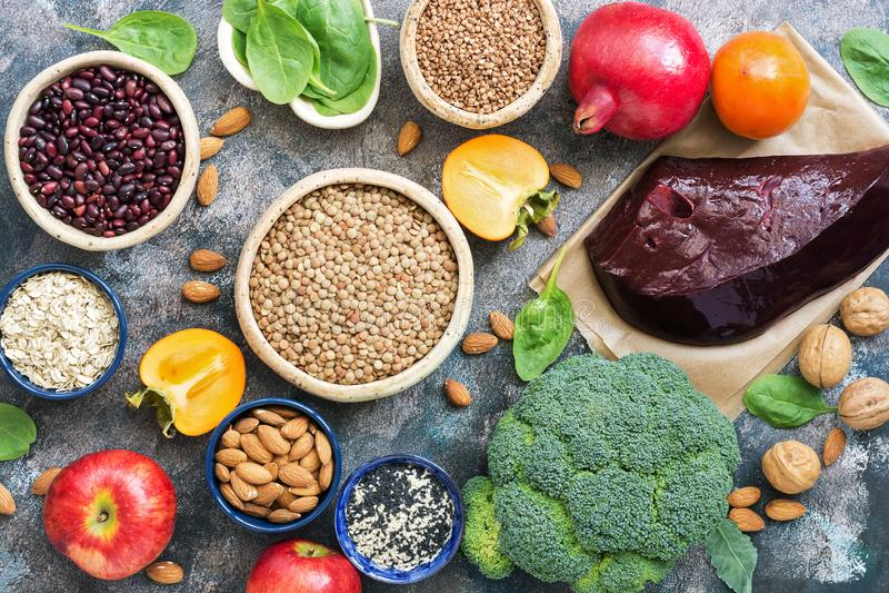 Voedsel hoog in Ijzer lever, broccoli, dadelpruim, appelen, noten, peulvruchten, spinazie, granaatappel De hoogste vlakke mening, stock afbeelding
