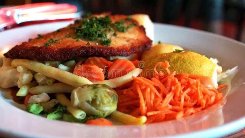 Voedsel met een grote schnitzel en wortelen stock foto