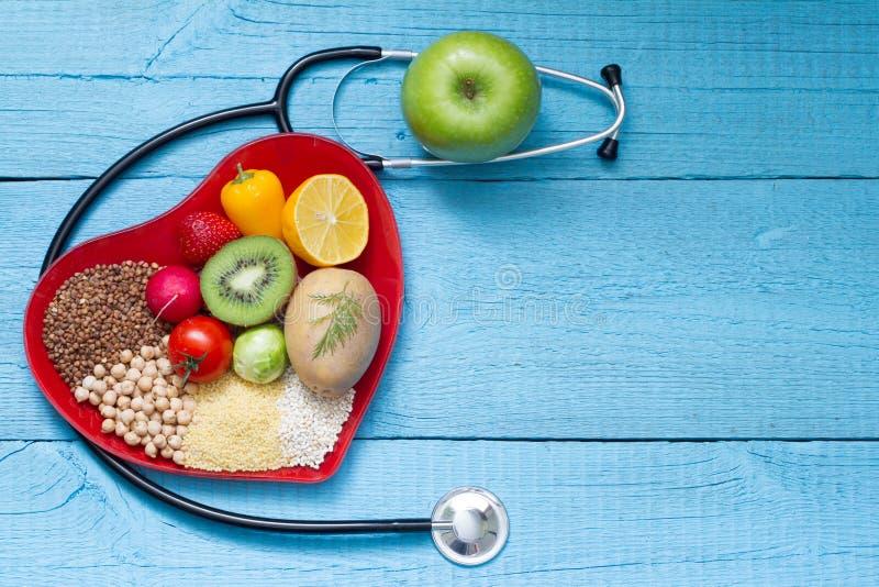 Voedsel op hartplaat met het concept van de stethoscoopcardiologie stock afbeeldingen
