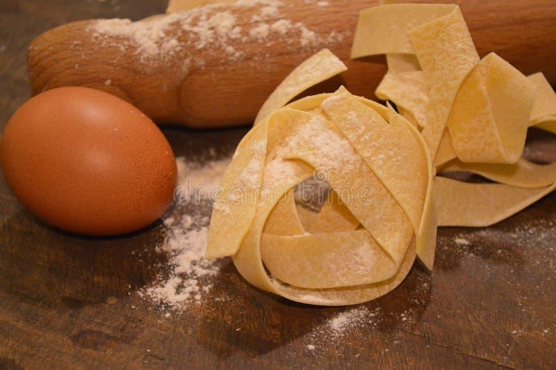 Voedsel van Tipical het Italiaanse deegwaren pappardelle freh eigengemaakt met eieren op lijst en keukengerei royalty-vrije stock afbeelding