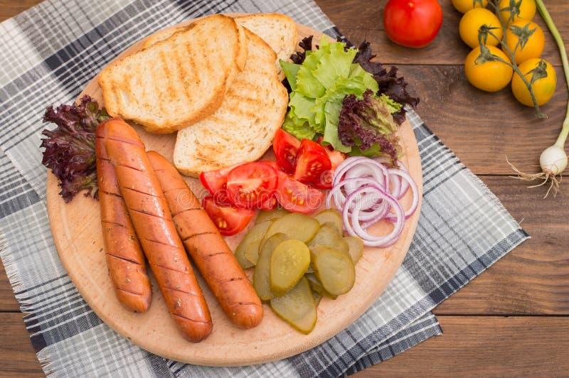Voedsel voor hotdog, worst, ingeblikte komkommers, slabladeren, tomaten, uien, croutons op de houten achtergrond wordt geplaatst  stock fotografie