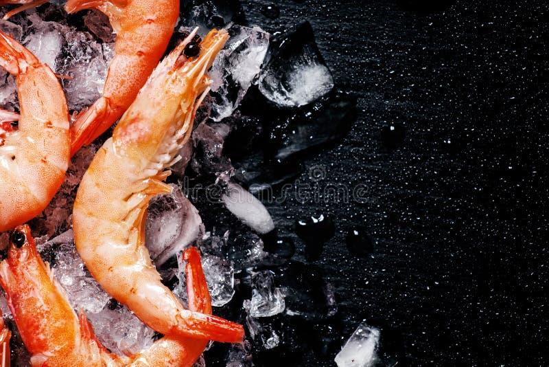 Voedselachtergrond, bevroren gekookte garnalen met ijs, zwarte achtergrond stock afbeelding