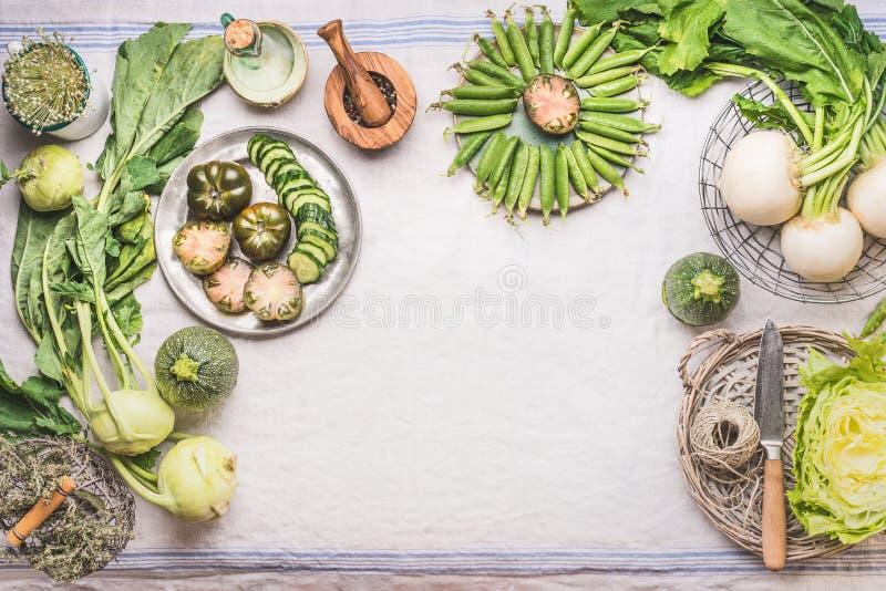Voedselachtergrond met groene groenten in kommen op lichte lijst met mes: groene erwten, koolraap, sla, courgette, groene komkomm royalty-vrije stock foto's