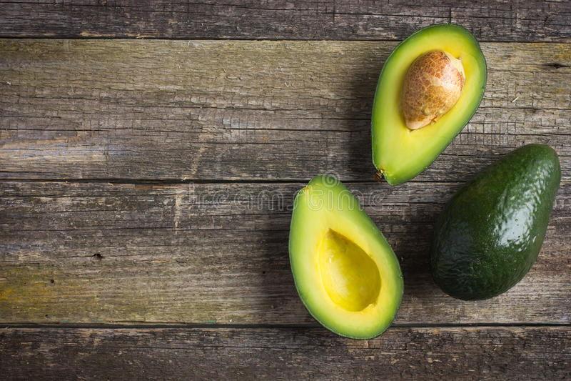 Voedselachtergrond met verse organische avocado op oude houten lijst royalty-vrije stock fotografie