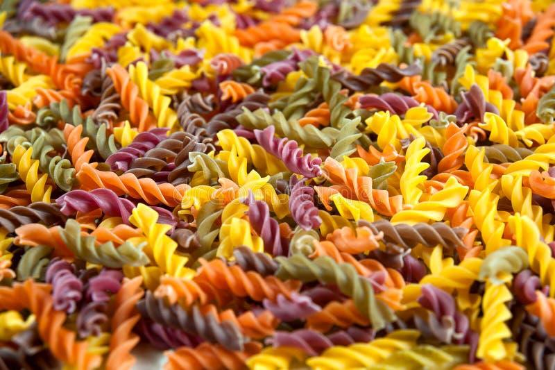 Voedselachtergrond - ongekookte drie-gekleurde Fusilli-durumtarwedeegwaren met spinazie en tomaat royalty-vrije stock foto