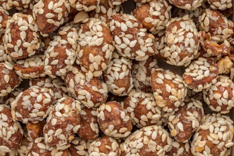 Voedselachtergrond van pinda's wordt gemaakt met glans worden en met sesamzaden worden bestrooid behandeld die dat royalty-vrije stock afbeelding