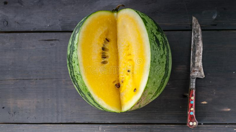 Voedselbanner Geel watermeloen en mes op een donkere houten achtergrond Hoogste mening stock foto