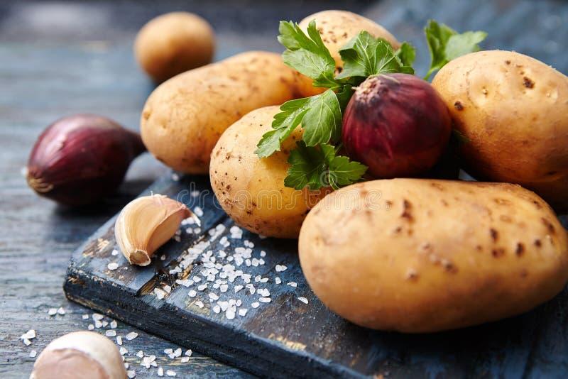 Voedselbanner Ruwe aardappels, uien, peterselie op een donkere houten lijst royalty-vrije stock fotografie