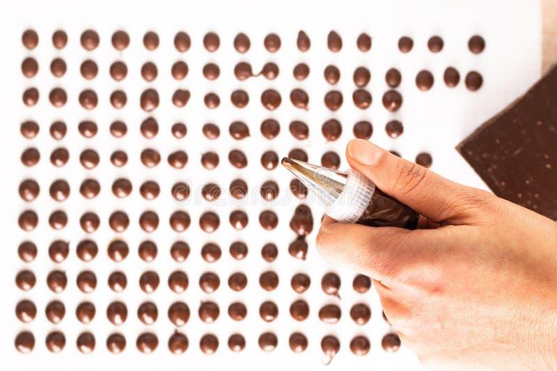Voedselconcept die eigengemaakte chocoladeschilfers voor bakkerij op witte achtergrond maken stock foto's