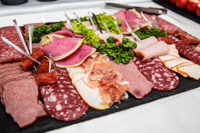 Voedseldienblad met heerlijke salami, stukken van gesneden ham, worst, salade - Vleesschotel met selectie stock afbeelding