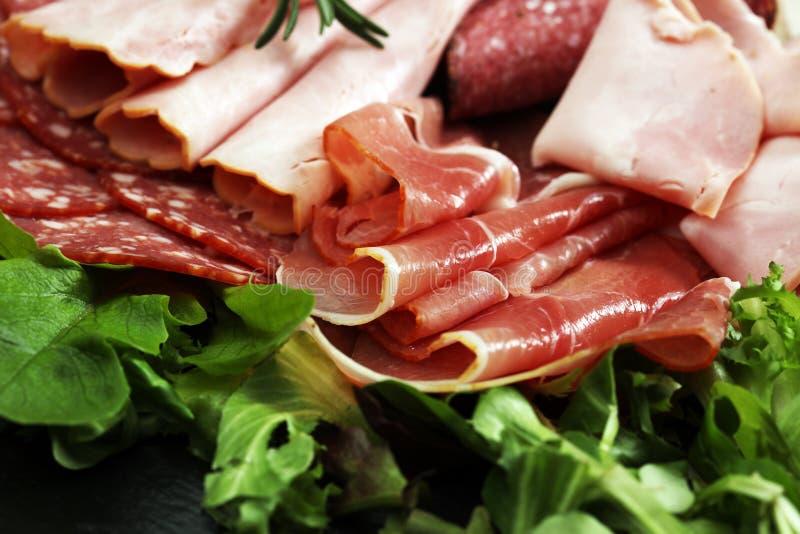 Voedseldienblad met heerlijke salami, stukken van gesneden ham, worst, tomaten, salade en groente - Vleesschotel met selectie royalty-vrije stock afbeeldingen