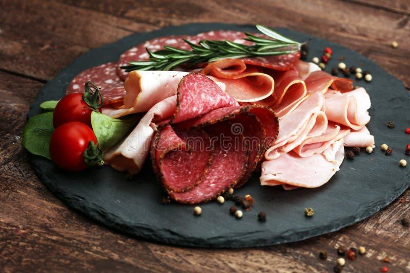 Voedseldienblad met heerlijke salami, stukken van gesneden ham, worst, tomaten, salade en groente - Vleesschotel met selectie stock afbeelding