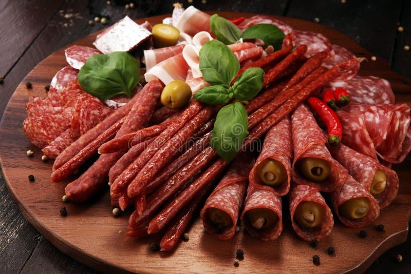 Voedseldienblad met heerlijke salami, stukken van gesneden prosciuttocru royalty-vrije stock foto's