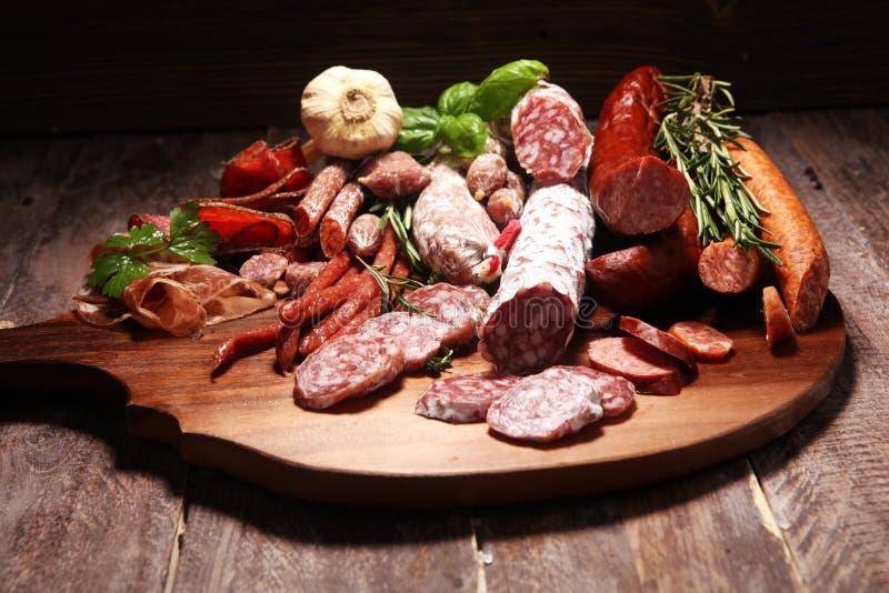 Voedseldienblad met koud vlees met heerlijke salami en kruiden Verscheidenheid van vleeswaren met inbegrip van coppa en worsten stock foto