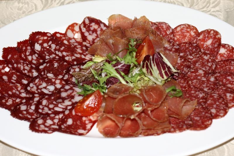 Voedseldienblad met salami, stukken van gesneden ham, worst, tomaten, salade en groente - Vleesschotel met selectie die - snijden stock foto