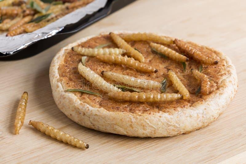 Voedselinsecten: Bamboeworm voor het eten als voedsel De bakkerij bakte brood dat van gekookte insect en bamboerupsband in baksel stock afbeeldingen
