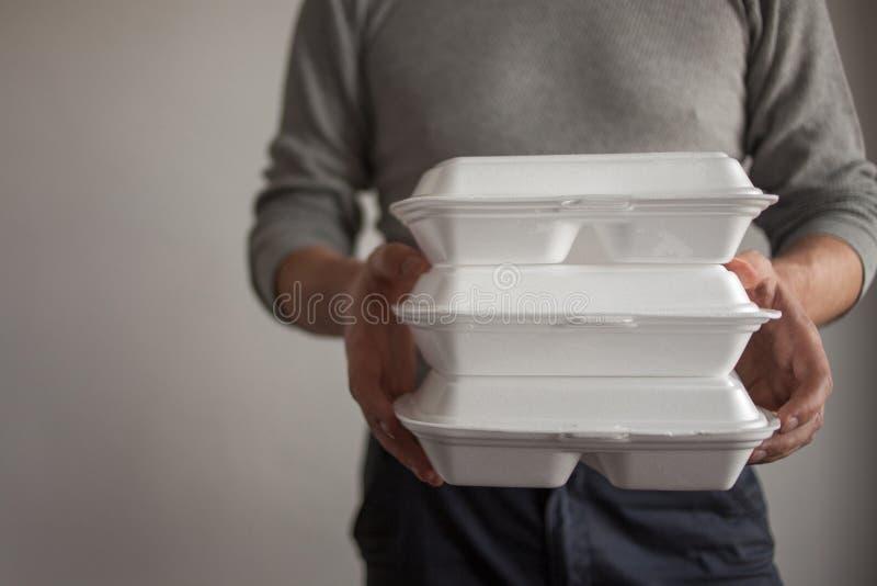 Voedsellevering De koeriersman die een container voedsel houden royalty-vrije stock fotografie