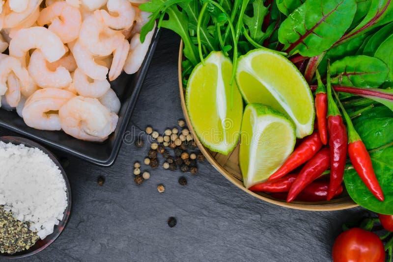 Voedselsamenstelling van garnalengroenten en kruiden op zwarte steenachtergrond stock afbeeldingen