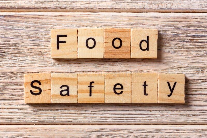 Voedselveiligheidwoord op houtsnede wordt geschreven die Voedselveiligheidtekst op lijst, concept stock foto's