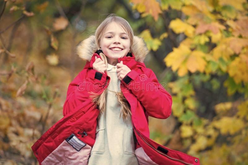 Voel zo comfortabel in warm jasje Het lange haar die van het kindblonde in warm jasje lopen openlucht Het meisje gelukkig in laag stock afbeeldingen