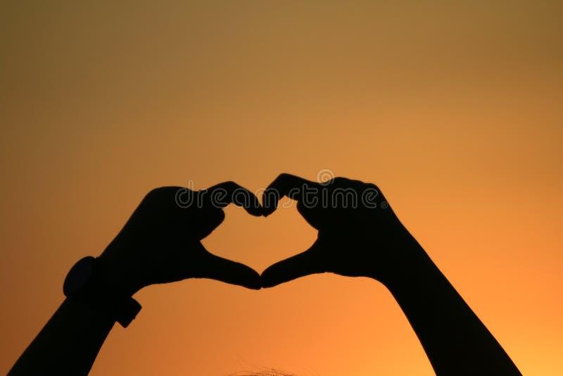Voelen de hart gemaakte handen die hartvorm met gouden zonsondergangsilhouet vormen, Schaduw van de liefdetekens van de vrouwenha stock afbeeldingen