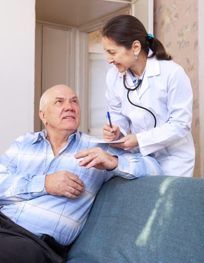 Voelt de arts gevraagde mannelijke rijpe patiënt stock foto's