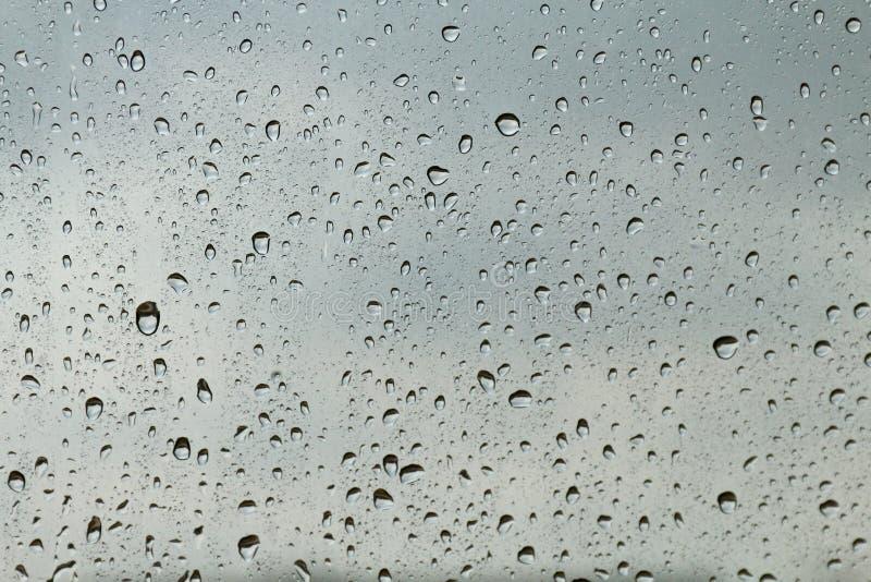 Voelt de verse condensatie van de waterdaling op de textuur van het vensterglas, het regenachtige seizoen natte koelen als achter royalty-vrije stock afbeelding