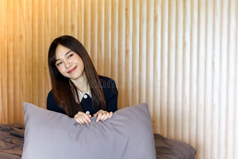 Voelt het Aziatische leuke meisje van de schoonheidsvrouw gelukkige het glimlachen het genieten van tijd op haar slaapkamerachter stock afbeeldingen