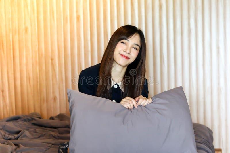 Voelt het Aziatische leuke meisje van de schoonheidsvrouw gelukkige het glimlachen het genieten van tijd op haar slaapkamerachter stock foto's