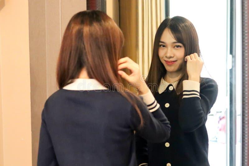 Voelt het Aziatische leuke meisje van de schoonheidsvrouw gelukkige het glimlachen het genieten van tijd op haar slaapkamerachter stock foto