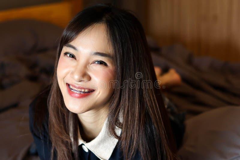 Voelt het Aziatische leuke meisje van de schoonheidsvrouw gelukkige het glimlachen het genieten van tijd op haar slaapkamerachter royalty-vrije stock afbeelding