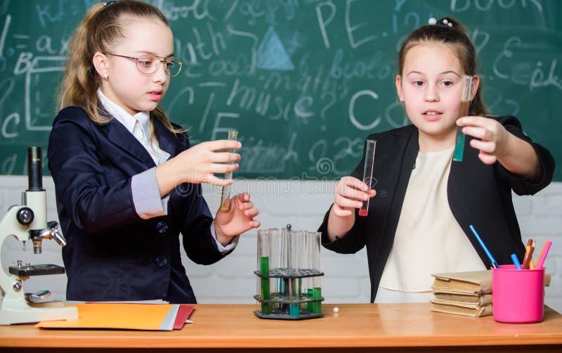 Voer chemische reacties uit Basiskennis van chemie De meisjesklasgenoten bestuderen chemie Maak het bestuderen van chemie stock fotografie