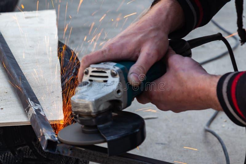 Voert de sterke de mensenmeester van de close-upmening zonder handschoenen op wapens, om metaal te snijden met een hoekmolen in u stock afbeelding