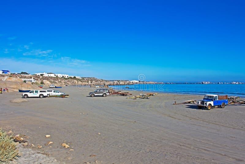 Voertuigen en bootaanhangwagens op strand worden geparkeerd dat royalty-vrije stock foto