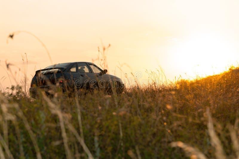 Voertuigparkeren op de weide bij zonsondergang stock afbeelding