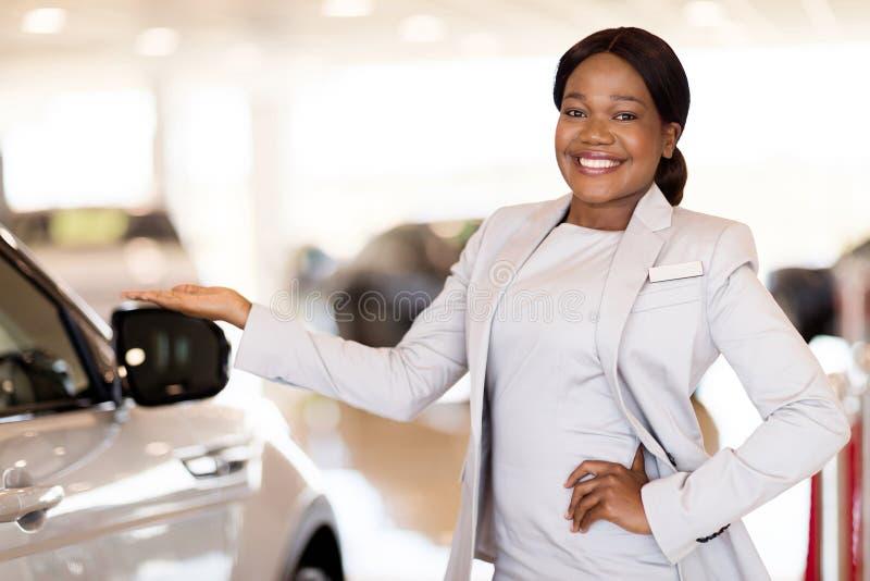 Voertuigverkoopster die auto's voorstellen royalty-vrije stock afbeelding