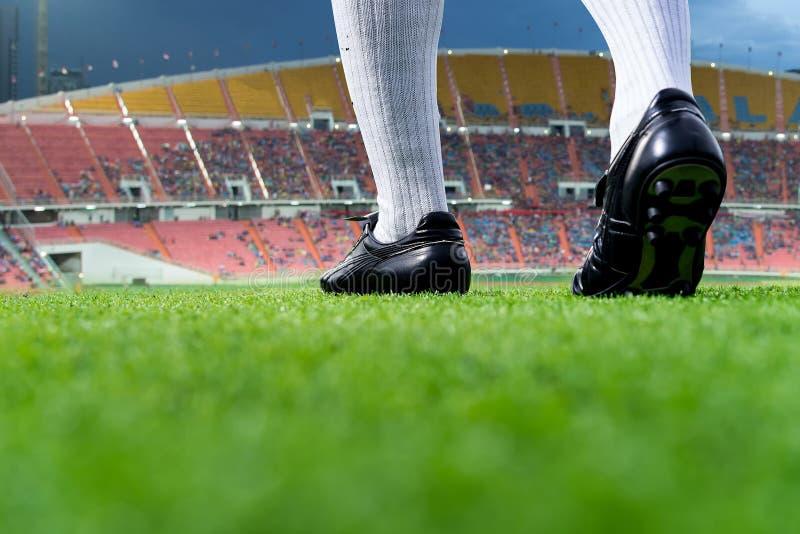 Voet van voetballer of voetbalstergang op groen gras stock afbeeldingen