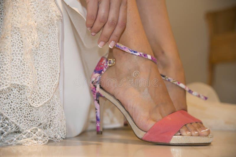 Voet van vrouw, gekleed als bruid en het zetten op de schoen royalty-vrije stock afbeelding