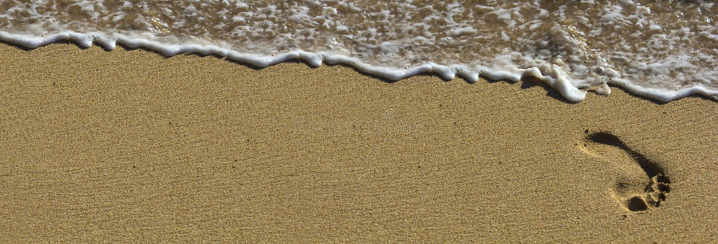Voetafdruk bij strand met golven stock foto