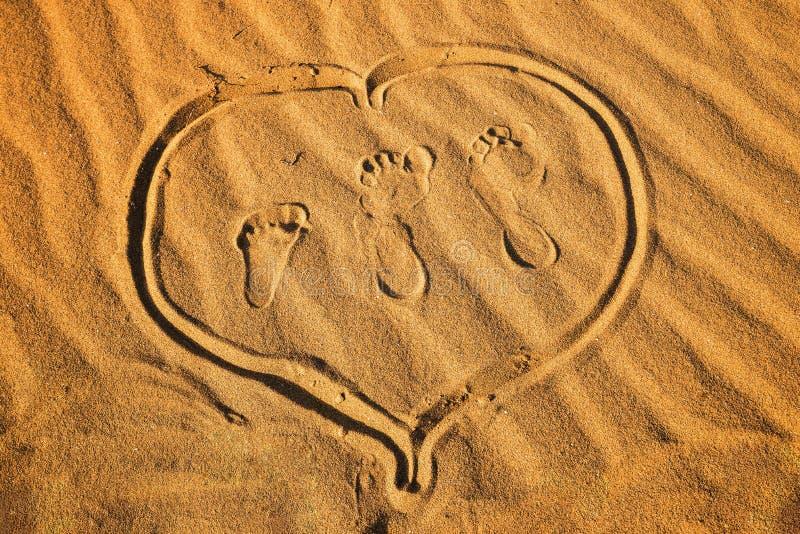 Voetafdruk drie en hart op zand stock foto's