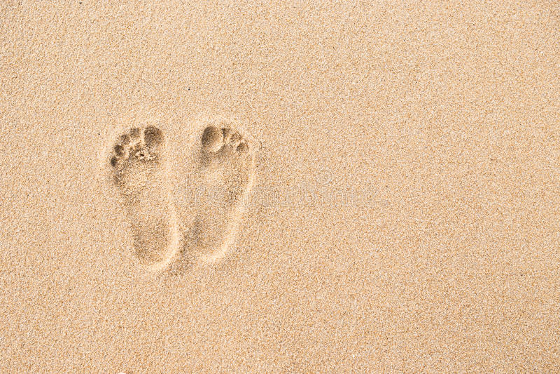 Voetafdruk op strand op zandachtergrond stock foto