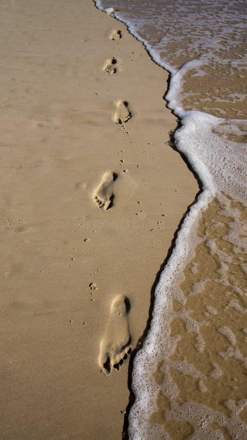 Voetafdrukken in het zand met golven stock fotografie