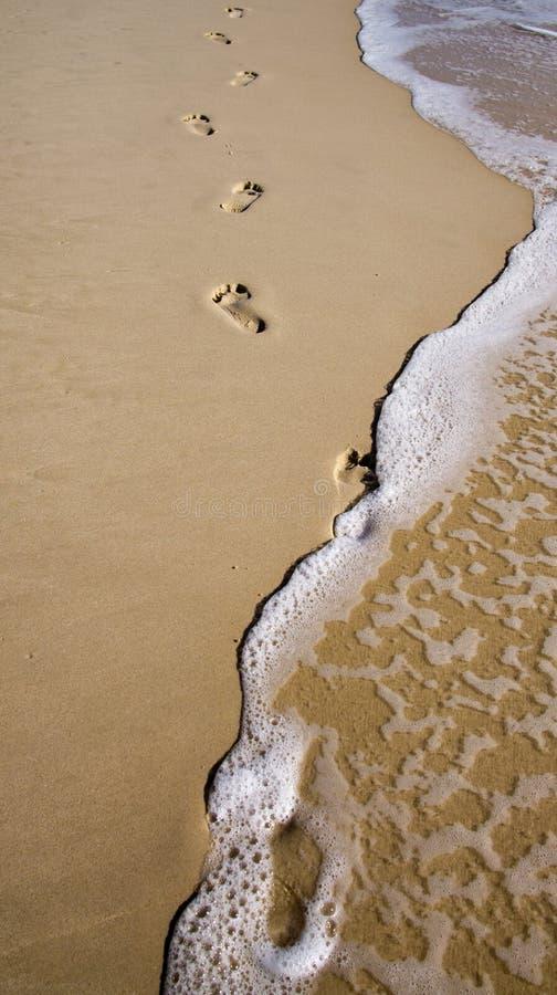 Voetafdrukken in het zand met golven stock afbeeldingen