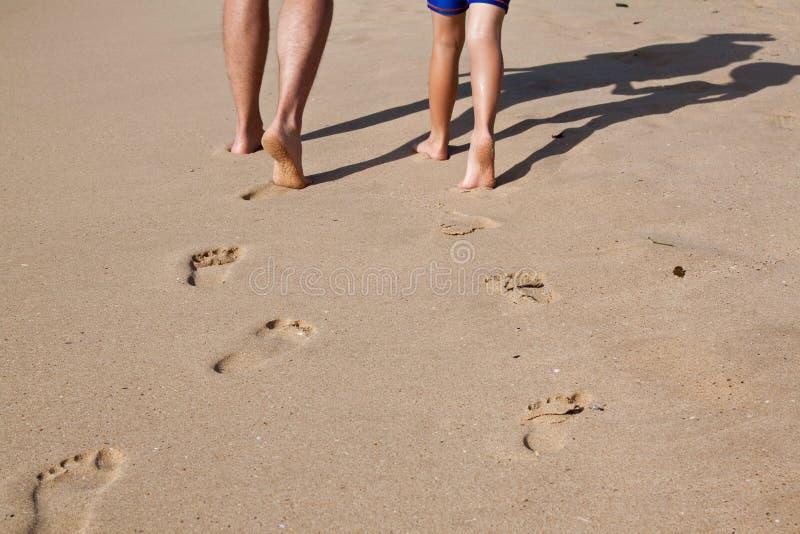 Voetafdrukken in nat zand van vader en zoon stock foto
